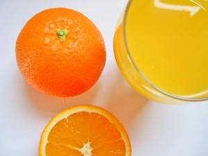Mandarinas junto a un vaso de zumo de mandarina