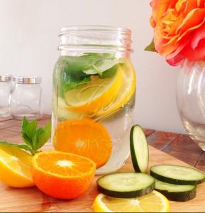 Recipente con rodajas de frutas y agua para preparar agua detox.