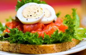 Tosta de pan integral con lechuga, salmón ahumado y buevo duro.